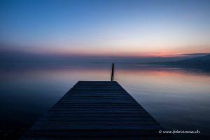 Holzsteg zur blauen Stunde vor Sonnenaufgang am See